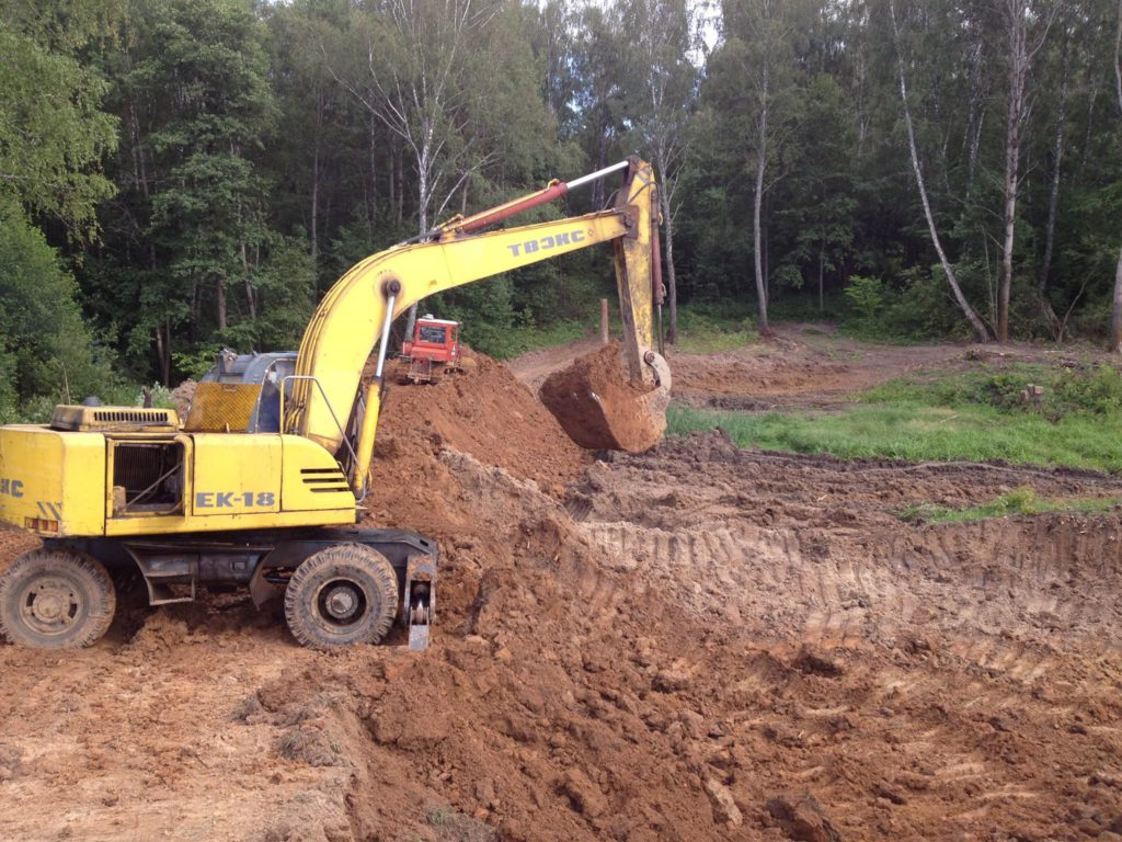 тяжелая техника на строительстве пруда